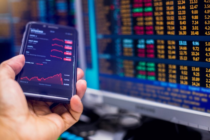 Close up of a phone open to a trading app with a large chart of stock prices in the background.
