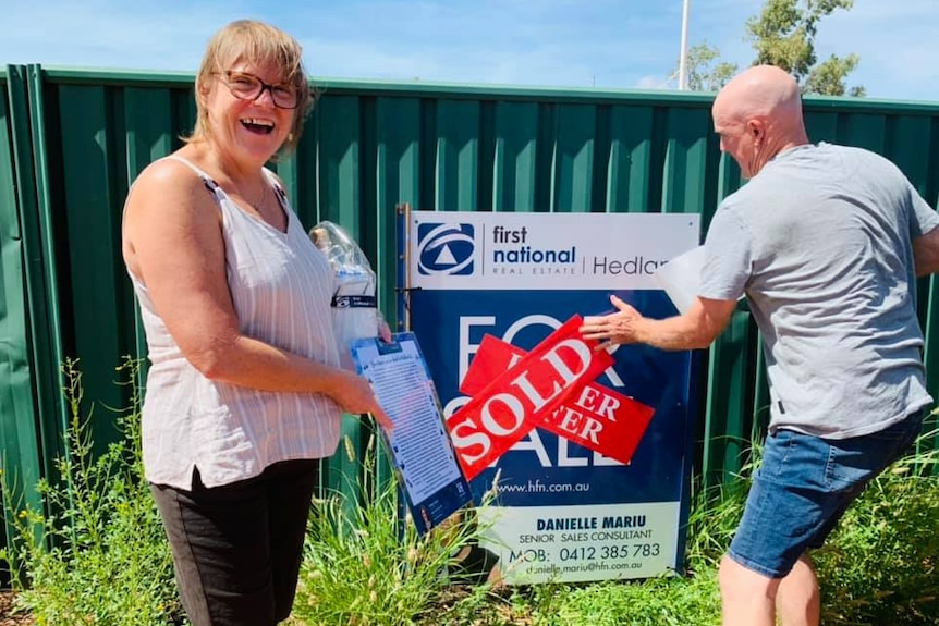 A woman and a man stand in front of a sign for sale on a green fence, with the man putting a red `` sold '' sticker on the sign.