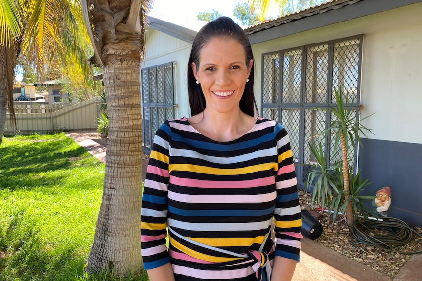 Mid shot of a smiling woman standing in the yard of a house with a tree and the house behind her.