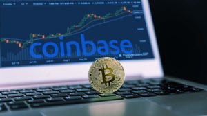 A Bitcoin is based on a computer with the Coinbase logo (COIN) and a trading chart.